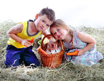 The girl with the boy on hay iron a favourite. Girl, boy, basket carrots hay rabbit hare weaving, rod Royalty Free Stock Photo