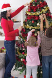 Girl and boy helping her mother decorating the Christmas tree Royalty Free Stock Photo