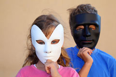 Girl and boy hide faces behind masks Royalty Free Stock Photography