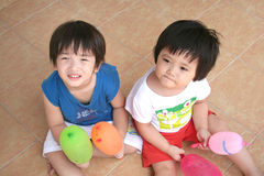 Girl & boy holding balloons. Sitting on the floor royalty free stock images
