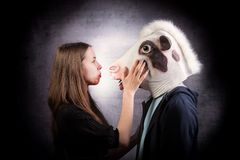 Girl and boy with horse head. Strange couple concept. Studio shot on grey background Royalty Free Stock Photography