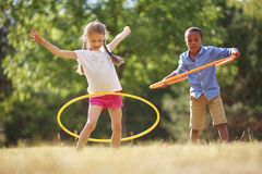Girl and boy with hula hoop. Playing at the park stock photography