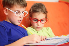 Girl and boy intently doing homework. Focus on the hinge glasses Royalty Free Stock Image