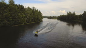 Girl and boy on the jet ski in the river.Aerial video. stock footage