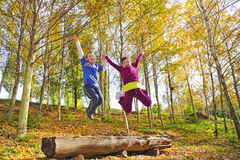 Girl and boy jumping. In forest in autumn time Royalty Free Stock Image