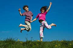 Girl and boy jumping Stock Images