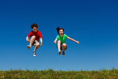 Girl and boy jumping. Against blue sky royalty free stock image