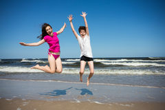 Girl and boy jumping on beach Stock Image