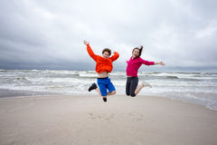 Girl and boy jumping on beach. Teenage girl and boy running, jumping on beach Stock Image