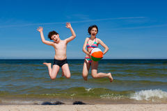 Girl and boy jumping on beach Stock Images