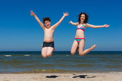 Girl and boy jumping on beach Stock Photos