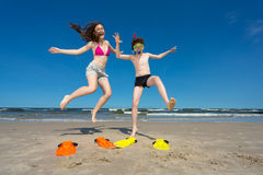 Girl and boy jumping on beach Royalty Free Stock Photos