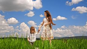 Girl And Boy Jumping In Green Field. This is a shot captured in the field - pretty girl with long brown hair in white sundress and small boy jumping on stock footage