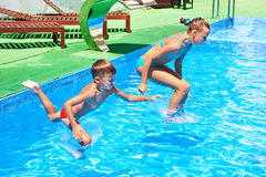 Girl and boy jumping into resort pool Stock Photos