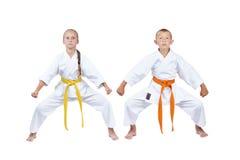 Girl and boy in karategi standing in rack kiba dachi Stock Images