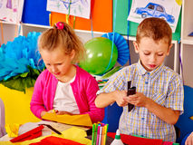 Girl and boy kids cut paper on table in kindergarten . Royalty Free Stock Images