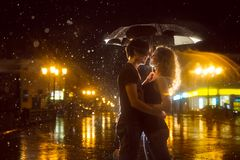 The girl with the boy kissing under a down-pour rain Royalty Free Stock Photography