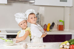 Girl and boy in the kitchen, posing back to back. Cute girl and boy proud to wear chef uniform while baking in the kitchen, posing back to back with folded arms royalty free stock photos