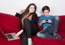 Girl and boy with laptop and phone. Teenage girl and a boy looking at a laptop and phone stock image