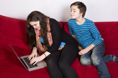 Girl and boy and a laptop. Teenage girl and a boy looking at a laptop royalty free stock photos