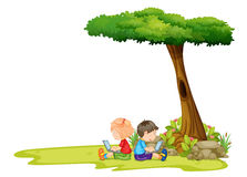 A girl and a boy with laptops under the tree Royalty Free Stock Photography