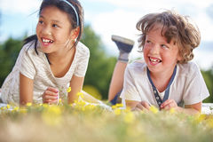 Girl and boy laughing. And picking up flowers Stock Photos