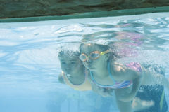 Girl and boy learning to swim Stock Images