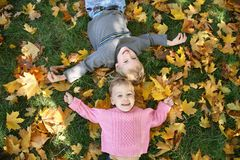 Girl and boy lie on grass Stock Photos