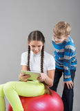 Girl and boy looking at a Pad Tablet PC screen Stock Photography