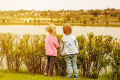 A girl and a boy looking to another bank of the river at a sunset. Stock Image