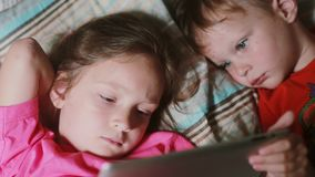 Girl and boy lying on the bed and watching cartoon on touchscreen tablet. Brother and sister having rest together. Two little kids, girl and boy lying on the stock video footage