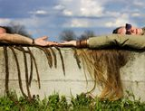 Girl and boy lying on a concrete wall Stock Photo