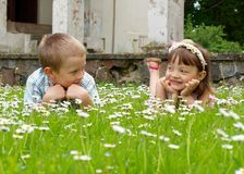 Girl and boy lying on the grass Royalty Free Stock Photos