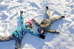 Girl and boy lying on snow Stock Photography
