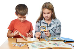 Girl and boy with magnifier looking his stamp collection isolate Royalty Free Stock Images