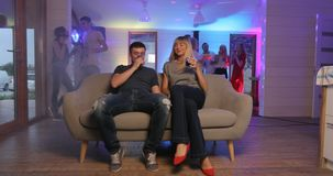 A girl and a boy are making cheers at the party. A girl and a boy are sitting on a couch making cheers at the party, girl kisses him in cheeck stock video footage
