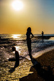 The girl and the boy on a marine beach against the sunset sun Royalty Free Stock Image