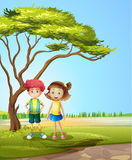A girl and a boy near a big tree Royalty Free Stock Photo
