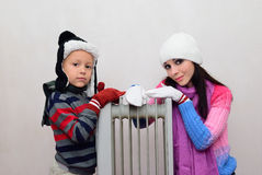 Girl and boy near a radiator heated Royalty Free Stock Photography