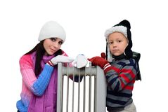 Girl and boy near a radiator heated Royalty Free Stock Images