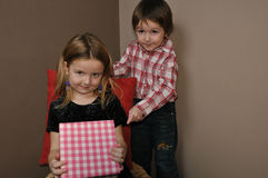 Girl with boy open gift box. On the corner with brown walls Royalty Free Stock Image