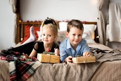 Girl and boy open gifts. Merry Christmas and Happy Holidays. stock photo