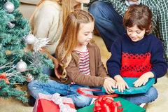 Girl and boy opening christmas Stock Photography
