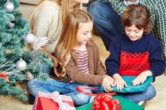 Girl and boy opening christmas Stock Photography