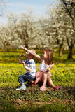 Girl with boy in a orchard Stock Image