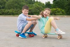 Girl and boy in the Park outdoors, riding sitting on sports boards, building funny grimaces stock photo