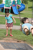 Girl & boy in the park swinging. Girl & boy playing in the park, swinging happily stock images