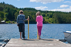 Girl and boy on the pier. The picture from the back of the girl and boy standing on pier stock image