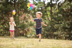 Girl and boy with pinwheels. Running and having fun Royalty Free Stock Photography