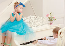 The girl and the boy play the piano Stock Photo